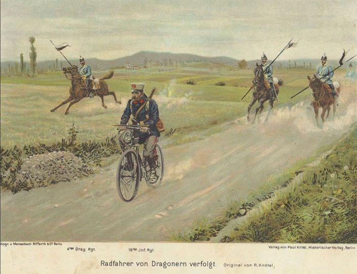 Una postal de preguerra que muestra un ciclista alemán frente a un grupo de Dragones Prusianos